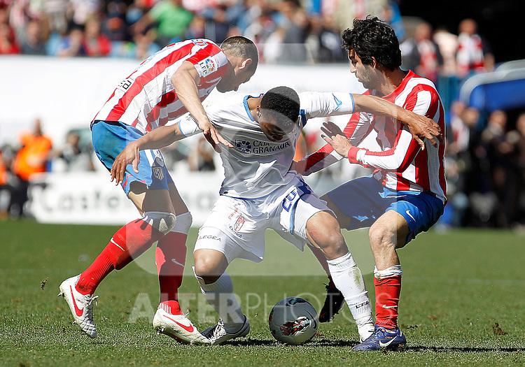 Atletico de Madrid's Alvaro Dominguez (l) and Arda Turan (r) and Granada's Ikechukwu Uche during La Liga match.March 11,2012. (ALTERPHOTOS/Acero)