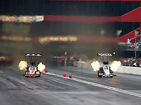 Jun 20, 2015; Bristol, TN, USA; NHRA top fuel driver Doug Kalitta (left) races alongside Antron Brown during qualifying for the Thunder Valley Nationals at Bristol Dragway. Mandatory Credit: Mark J. Rebilas-