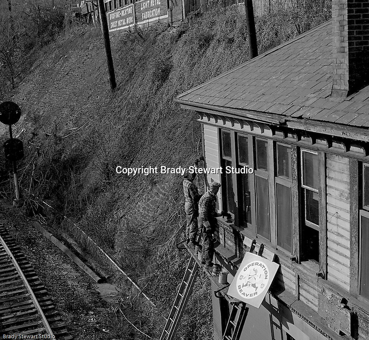 """Corliss PA:  View of PA Railroad workers restoring a building as part of the company's Operation Beaver. """"Operation Beaver,"""" was a paint-up, fix-up, and clean-up<br /> program of stations and cars intended to cosmetically cover deferred maintenances. Special posters and buttons were prepared as part of the campaign.<br /> These photos were used in a company newsletter to introduce the program company-wide."""