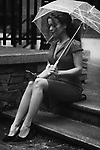 Young woman in an elegant dress sitting on the stairs with an umbrella in the rain on a city street with a phone in her hand Black and white photo