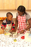4 year old boy cooking with mother learning how to make traditional corn meal dish