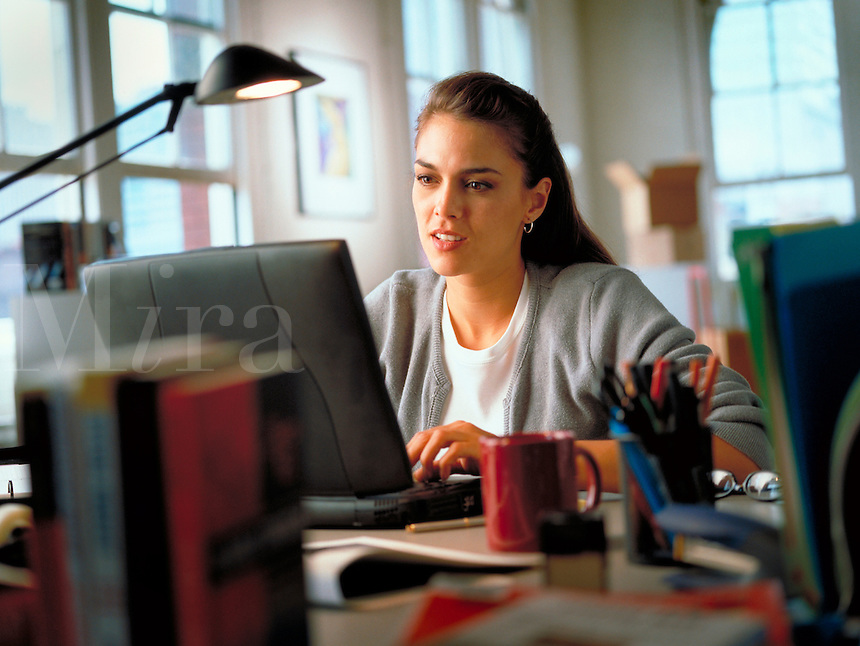 Young woman working on a laptop computer at her desk in her home office. Billboard and broadcast must be negotiated, due to talent agreement.