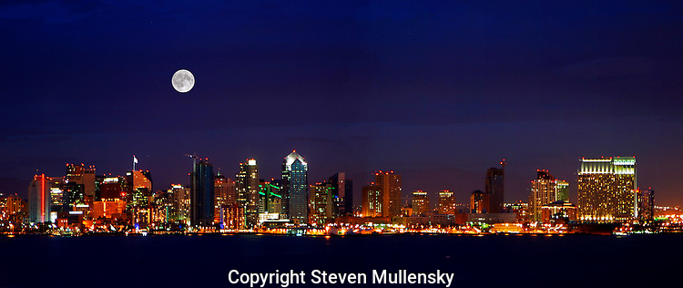 A full moon rises over the harbor and downtown of San Diego, California