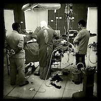 Hospital in Derik, Rojava/Syrien.<br /> Trotz etlichen kaputten Geraeten ist das Krankenhaus in Derik eines der bestausgeruesteten Hospitaeler im Kanton.<br /> Im Bild: Aerzte operieren eine schwerverletzte Kaempferin der YPG/YPJ, die bei den Kaempfen in der Stadt Haseker durch einen Schuss in den Ruecken lebensgefaehrlich verletzt wurde. Die Kugel drang bis in den Bauch und verletzte mehrere Organe. Den Aerzten gelang es ihr Leben zu retten.<br /> 17.12.2014, Derik/Rojava/Syrien<br /> Copyright: Christian-Ditsch.de<br /> [Inhaltsveraendernde Manipulation des Fotos nur nach ausdruecklicher Genehmigung des Fotografen. Vereinbarungen ueber Abtretung von Persoenlichkeitsrechten/Model Release der abgebildeten Person/Personen liegen nicht vor. NO MODEL RELEASE! Nur fuer Redaktionelle Zwecke. Don't publish without copyright Christian-Ditsch.de, Veroeffentlichung nur mit Fotografennennung, sowie gegen Honorar, MwSt. und Beleg. Konto: I N G - D i B a, IBAN DE58500105175400192269, BIC INGDDEFFXXX, Kontakt: post@christian-ditsch.de<br /> Bei der Bearbeitung der Dateiinformationen darf die Urheberkennzeichnung in den EXIF- und  IPTC-Daten nicht entfernt werden, diese sind in digitalen Medien nach §95c UrhG rechtlich geschuetzt. Der Urhebervermerk wird gemaess §13 UrhG verlangt.]