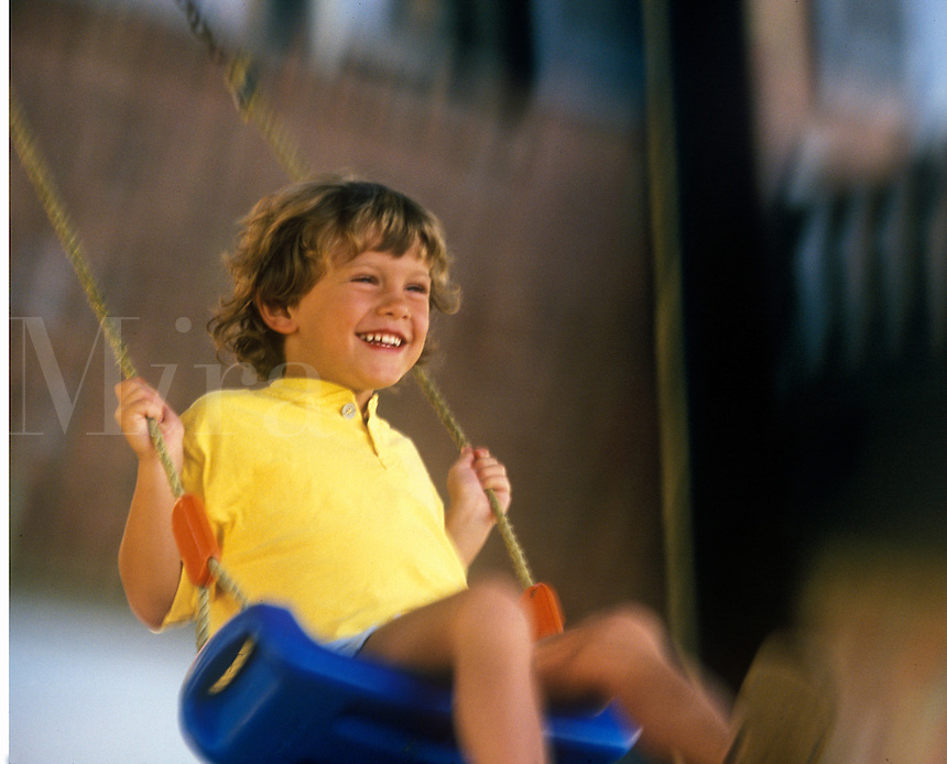 Delighted boy on swing.