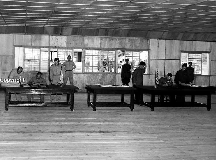 Gen. W. K. Harrison, Jr., signs armistice ending 3-year Korean conflict.  Gen. Harrison, left table, and North Korean Gen. Nam II, right table, sign documents.  July 23, 1953.  F. Kazukaitis. (Navy)<br /> NARA FILE #:  080-G-625728<br /> WAR & CONFLICT BOOK #:  1517