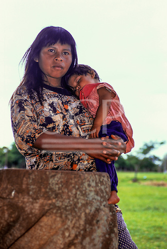 Rio Grande do Sul, Brazil. Guarani indian mother with sleeping daughter on her shoulder, looking into the camera.
