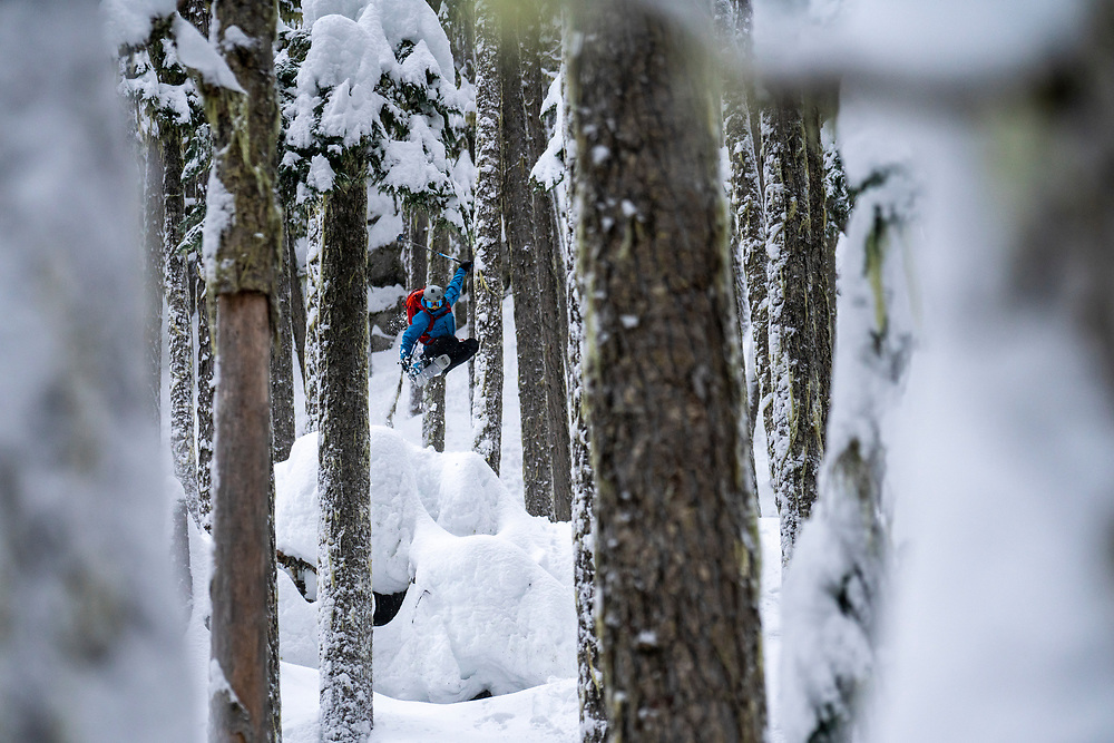 Andrea Byrne jumping for joy in the trees of Whistler