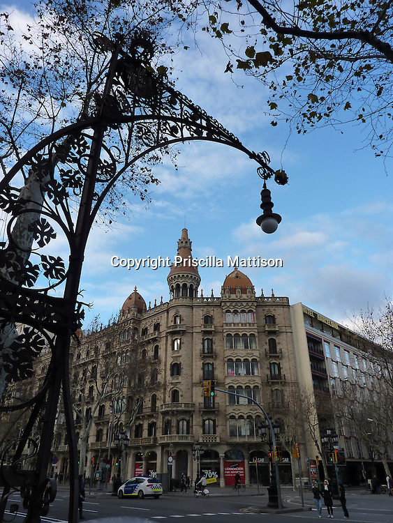 Barcelona, Spain - January 30, 2011:  An ornate street light and an orange-domed building enhance an intersection on Passeig de Gracia.