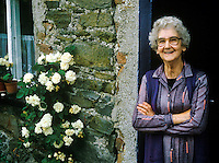 Smiling Irish woman at the door of her cottage home, Ramelton, County Donegal, Ireland