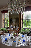 Abundant plants placed in the windows of this dining room lead the eye out into the lush greenery of the garden
