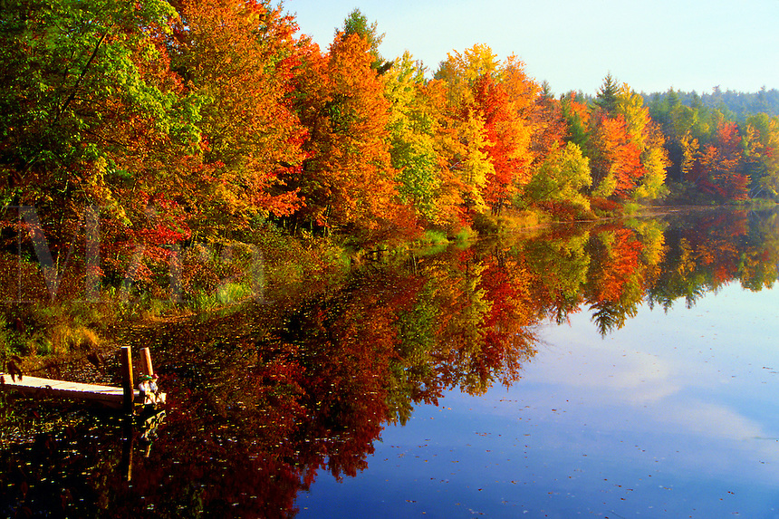 A peaceful jetty overlooks the scenic view of fall foliage along the Contoocook River on a misty morning. New Hampshire.