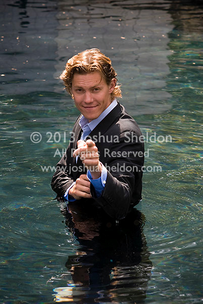 Young man wearing business suit standing in water pointing at camera