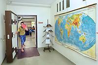 giovane iracheno  nel centro per asilanti, richiedenti asilo politico,in un ex bunker a Biasca, Canton Ticino, Svizzera. Cartina geografica del mondo
