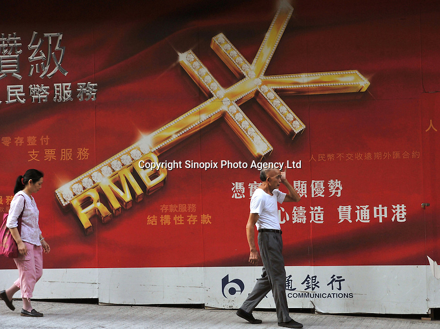 A local passes a huge poster advertising the Chinese currency the RMB outside the Bank of Communications in Western District, Central, Hong Kong. The RMB has appreciated almost 20% against the US dollar since the peg was dropped and it was allowed to be traded on the world markets, making the cost of producing in China much more expensive, forcing low-end manufacturers into bankruptcy..
