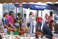 A street performer band playing Latin music on big drums with a group of young girls dancing and celebrating the bride-to-be the girl who is soon to be married hen's party, in the restaurant El Palenque, the sword fish swordfish, in the Mercado del Puerto, the market in the port harbour harbor where many people go and eat and shop on weekends Montevideo, Uruguay, South America