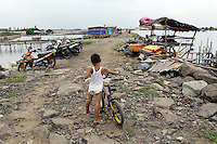 An Indonesian boy pushes his bike along a flood-wall in the port area of northern Jakarta.