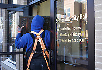 Sign installers Jesse Nielson carries a removed sign, Friday, February 19, 2021 at the old Bentonville City Hall in Bentonville. The signs will be repurposed to other city buildings. Check out nwaonline.com/210220Daily/ for today's photo gallery. <br /> (NWA Democrat-Gazette/Charlie Kaijo)