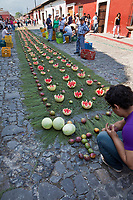 Antigua, Guatemala. Water melons and mangoes on a bed of pine needles make an alfombra in the street in advance of the passage of a procession during Holy Week, La Semana Santa.  The alfombra will be finished only a couple of hours before the passage of the procession, after which the remains will be quickly swept away by municipal street sweepers.