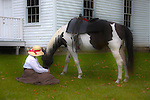 A woman and her horse enjoying the afternoon in front of the old school house GLOW