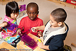 Education preschool 3-4 year olds group of two boys and a girl playing together in block area with plastic doll furniture and human figures discussing how to set it up working together horizontal