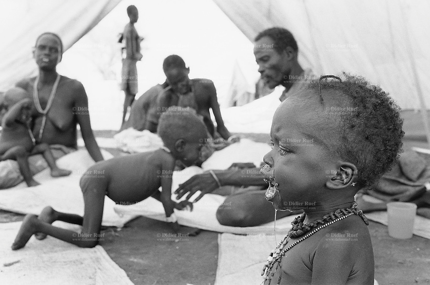 Sudan. Southern part. Bahr El Ghazal. Panthou. Dinka tribe area. Children and parents seat on the grounf under the tent in the feeding center ran by the ngo (non governmental organisation) MSF Holland ( Médecins Sans Frontières. Doctors without Borders). A child with necklace cries. © 1998 Didier Ruef