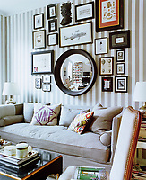 A diverse collection of artwork is displayed around a convex mirror above the sofa in the living room