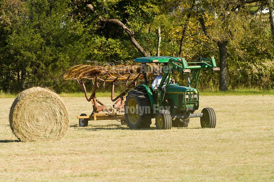John Deere tractors with roller-bail attachments, rake wheel preparing hay rolls in cut field 1997 model 5400.