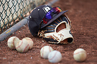 A Bryant Bulldogs cap sits on top of a glove surrounded by baseballs during the game against the High Point Panthers at Williard Stadium on February 21, 2021 in  Winston-Salem, North Carolina. The Panthers defeated the Bulldogs 3-2. (Brian Westerholt/Four Seam Images)