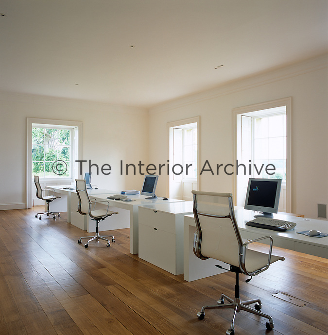 The minimalist office with white tables and retro-style chairs on a cleaned and resurfaced wooden floor