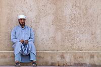 Oman, Buraimi, Arab man, seated against wall