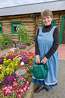 Linda Mereness, caretaker and docent at the Sullivan Roadhouse, tends to the flower garden, Delta Junction, Alaska.