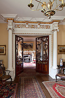 A grand doorway with elaborately carved glass doors lead out of the long hall and into an adjoining room