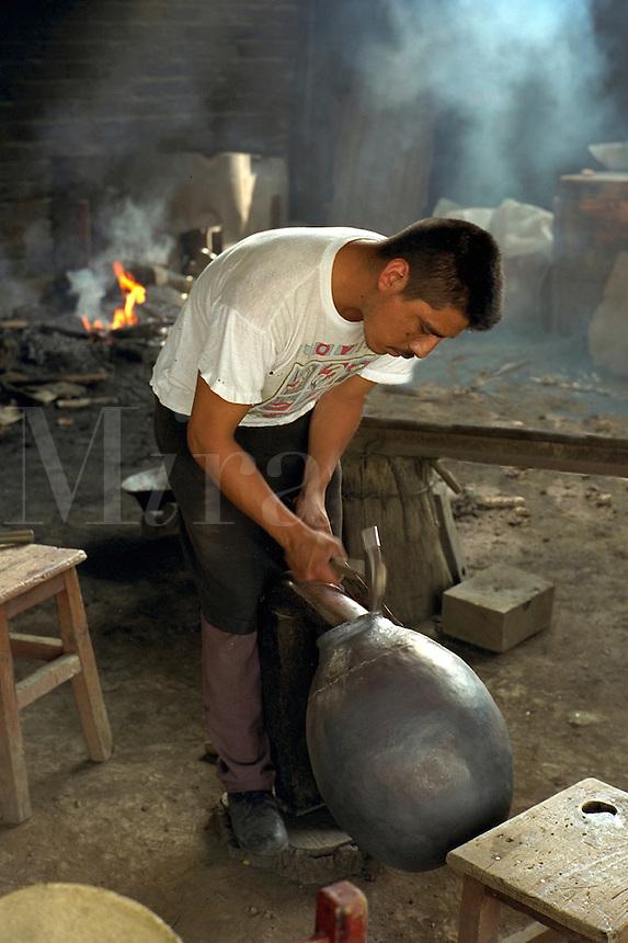 Copper worker shaping mouth of copper vessel by hammering. Santa Clara del Cobre Michoacan Mexico.