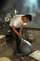 Copper worker shaping mouth of copper vessel by hammering. Santa Clara del Cobre Michoacan Mexico.