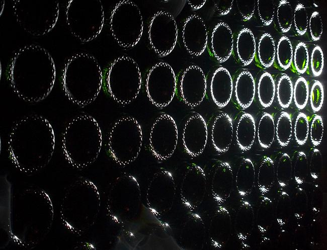Bottles of sparkling wine wait for labeling