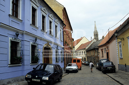 Bratislava, Slovakia. Quiet paved street with colourful buildings, a pedestrian and parked cars.