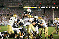 State College, PA -- 09/8/2007 -- Running back Austin Scott (33) leaps over the goal line and Irish linebacker Toryan Smith (49) to score a touchdown in the third quarter, making the score 23-10.  Scott was led by lineman John Shaw (78), of Spring Grove, and center A.Q. Shipley (57).  Penn State defeated Notre Dame by a score of 31-10 on Saturday, September 8, 2007, at Beaver Stadium.    ..Photo:  Joe Rokita / JoeRokita.com