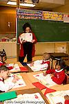 K-8 Parochial School Bronx New York Kindergarten female teacher talking to class about coins math class vertical
