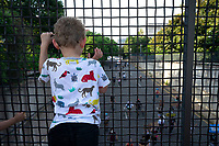 A child watches demonstrators march to Interstate 395 in Washington D.C., U.S., on Tuesday, June 23, 2020.  Trump tweeted that he authorized the Federal government to arrest any demonstrator caught vandalizing U.S. monuments, with a punishment of up to 10 years in prison.  Credit: Stefani Reynolds / CNP/AdMedia