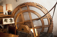 """Switzerland. Canton Ticino. Novaggio. The Vinera mill is on the """"Sentiero delle Meraviglie"""" which is a walking path.  The internal wooden wheel of the water mill. Drawing of an old couple, both farmers who were the previous owners of the mill. The """"Sentiero delle Meraviglie"""" is a guided trail which is plunged into nature, but every so often signs of human activity appear. Novaggio is located in the Malcantone area. 16.03.2010 © 2010 Didier Ruef"""