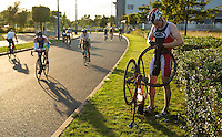 16 AUG 2014 - DARTFORD, GBR - John Buchanan from Crystal Palace Triathletes attempts to repair a puncture during his first bike lap during the 2014 Midnight Wo/Man triathlon in The Bridge area of Dartford, Great Britain (PHOTO COPYRIGHT © 2014 NIGEL FARROW, ALL RIGHTS RESERVED)