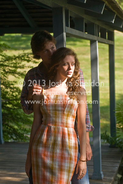 Couple standing together on porch, his hand on her shoulder