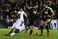 Tammy Abraham of Swansea City is knocked by Steve Cook of Bournemouth as he moves towards goal during the Premier League match between Swansea City and Bournemouth at the Liberty Stadium, Swansea, Wales, UK. Saturday 25 November 2017
