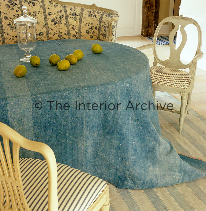 A detail of a pale blue dhurrie used as a tablecloth on the dining room table
