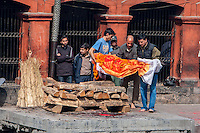 Nepal, Pashupatinath.  Cremation Stages.  Family Members Prepare to Place  the Corpse on the Cremation Site.  The body is covered with bright orange cloth and marigolds.