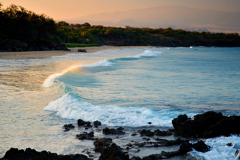 Waves and sunrise on Hapuna Beach with Hualalai volcano in background. Hawaii Island
