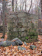 The remains of an abandoned granite foundation from the 19th - 20th century mountain settlement in the forest of Pawtuckaway State Park in Deerfield, New Hampshire USA.