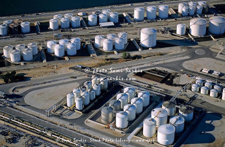 Oil tanks next to sea with railroad tracks.