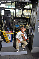 Local boy giving a shaka hand sign inside the cockpit of a plane at the Pacific Aviation Museum on Ford Island, Pearl Harbor, O'ahu.